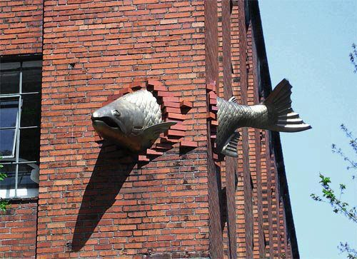 Transcendence, Fabricated Metal Fish Sculpture Through Corner of Brick Wall Building by Keith Jellum